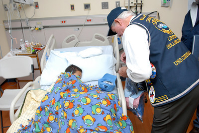 Dey Vaun Williams, 10, Williamsport, gets a cap and other goodies from veteran William Reasner, during a caps for kids program at the Janet Weis Children's Hospital in Danville on Monday, Veteran's Day.