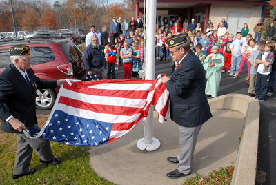 American Legion Post 44 members Paul Ruane, left, and Richard Simpson, perform a flag ceremony for a group of Priestly Elementary students on Monday for Veteran's Day.