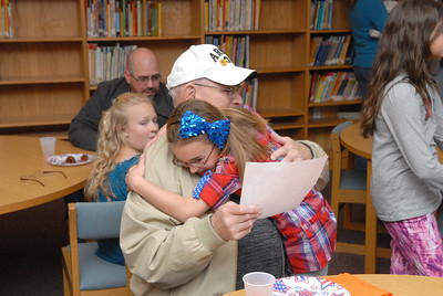 Army veteran Emerson Neidig, Sunbury, gets a hug from his great granddaughter Sophia Feathers, 8, at a Veteran's Day celebration at Priestly Elementary in Northumberland on Monday.