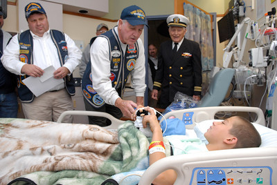 Veterans who all served on submarines, William Reasner, left, Don Young, and John Peterman, a WWII veteran, give a cap and some other goodies to Janet Weis Children's Hospital patient Kevin Bower Jr., 11, South Williamsport, during a caps for kids program on Veteran's Day in Danville.