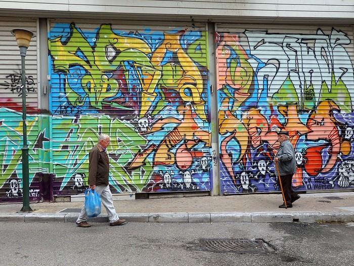Elderly Greek men walking by street art in Athens, Greece