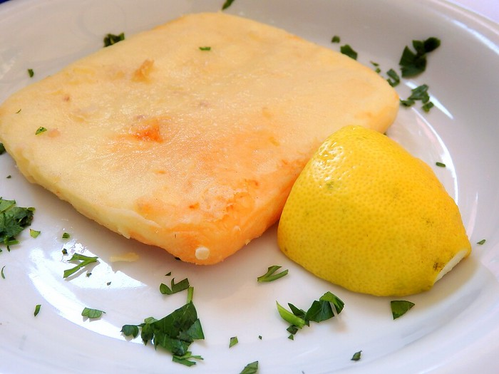 Saganaki, fried Greek cheese, with lemon for lunch in Athens, Greece