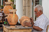 An artisan carves and paints clay pots near Corinth, Greece.