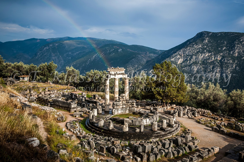 The Tholos Temple, Sanctuary of Athena ruins with rainbow in Delphi, Greece.