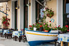 Restaurant table and chairs with local decor grace the waterfront at the attractive fishing town of Githeo, Greece.