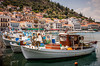 Pastel colored buildings on the waterfront and colorful fishing boats at the attractive fishing town of Githeo, Greece.