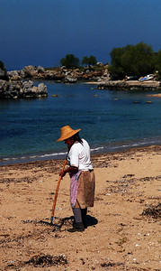 woman cleaning the beach, Stoupa, Peloponissos