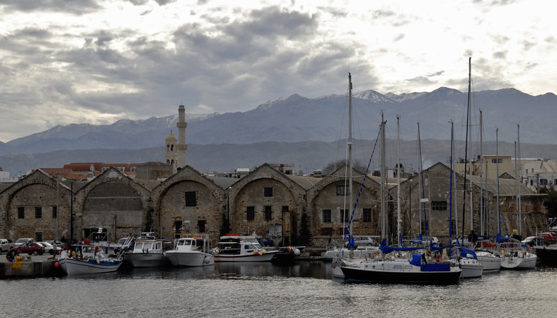 Great arsenal, Chania, Crete, Christmas Day 2009.     Here are six of the seven surviving warehouses built by the Venetians in the 16th century.   The Orthdox cathedral with its minaret and campanile are in the middle distance at left.  The White Mountains beyond.are some 2450m high.