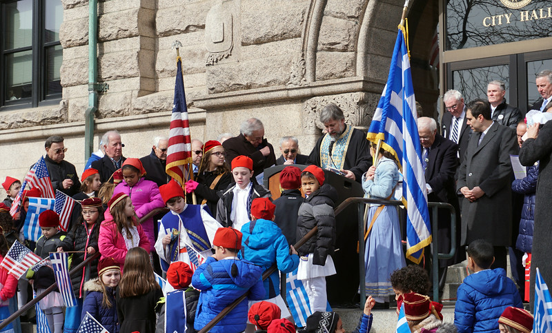 Rev. Father Nikolas Pelekoudas of Holy Trinity Greek Orthodox Chhurch giving speech about Greek Independence Day on the steps of Lowell City Hall. (The Sun / Chris Tierney)