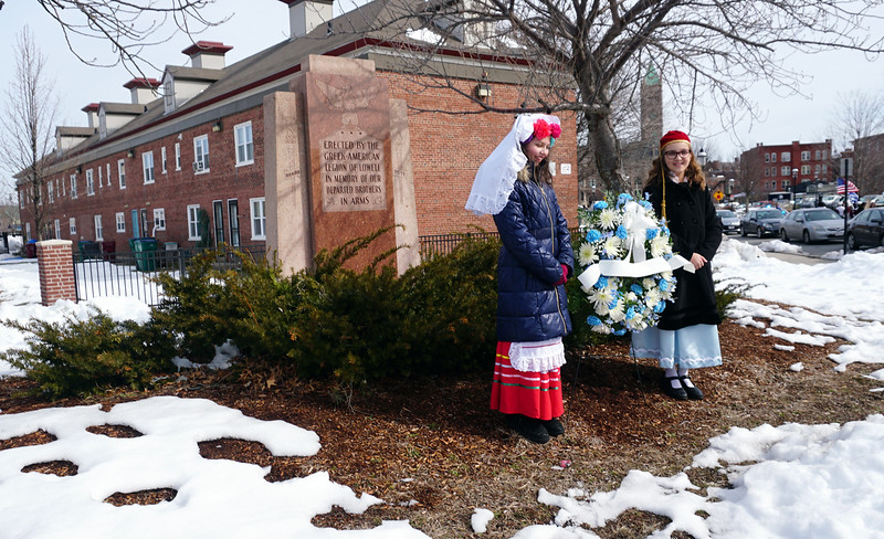 Ava Regan and Briana Hardy place a wreath in front of Greek monument on the corner of Broadway and Dummer Streets. (The Sun / Chris Tierney)