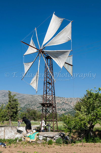 A couple washing their laundry beside a windmill on Lasithi Plateau in eastern Crete, Greece.