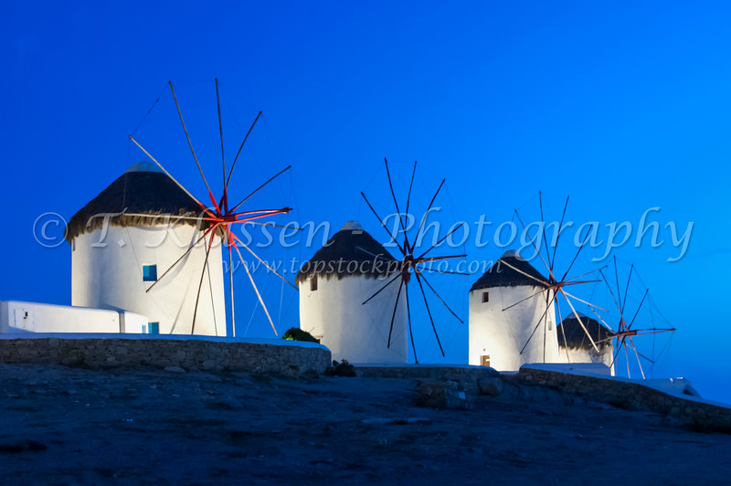 The windmills of Mykonos at dusk and sunset up on a hill at Hora or Mykonos town, Greece.