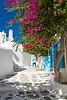 A street with overhanging bougainvillea flowers in Mykonos Town, Chora, Mykonos, Greece, Europe.