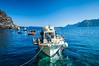 Colorful fishing boats in Amoudi Bay near Oia Thira, on the Greek Island of Santorini, Greece.