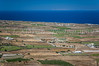 Island landscape of agricultural fields overlooking the Aegean Sea near Fira, Santorini, Greece.