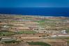 Island landscape of agricultural fields overlooking the Aegean Sea near Fira, Santorini, Greece.