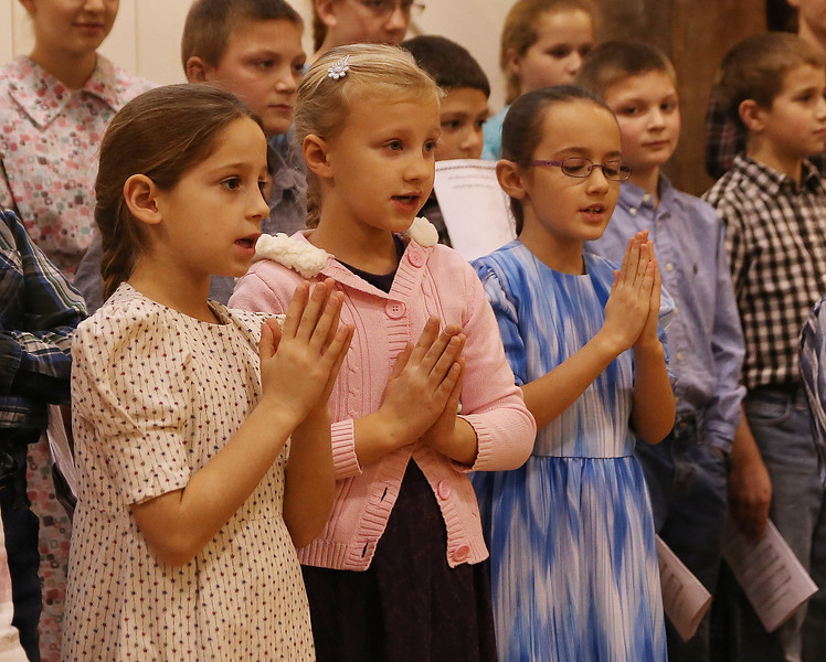 HOLLY PELCZYNSKI - BENNINGTON BANNER Lindsey Baer 7 years old, Annika Zimmerman 7 years old, and Makennah Hess 7 years old raise their hands in prayer while singing to seniors at Bennington Project Independance on Monday morning during a visit from students of The Green Mount Mennonite School.
