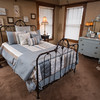 A century-old iron bed is the centerpiece of the master suite. An antique chest was repainted to complement the restful pale turquoise color scheme.