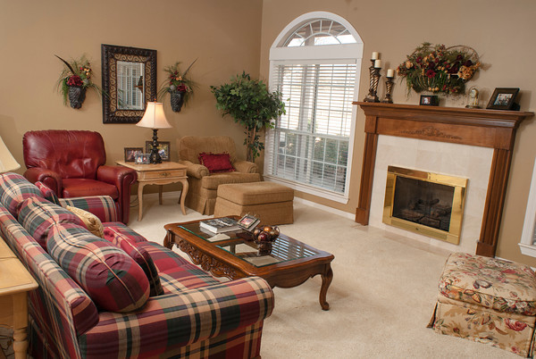 The furnishings in the Goad living room include  red leather chairs and plaid and floral fabrics on sofas and chairs. Each room in the home has a touch of red mixed with beige, off-white or gold.