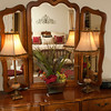 A winged mirror tops the dresser, reflecting the master suite.