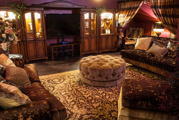 "Angela Scott says her theater room is the ""woman's cave."" It is ""really comfortable,"" she said of the room. The walls are painted dark burgundy with gold dust in the paint. A round cheetah-covered ottoman is in the center of the room."