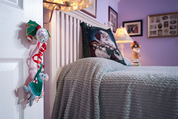 A mouse hangs from the doorknob by a candy cane in the entrance to the guest room.