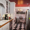 The Halbrook kitchen has a black-and-white tiled floor, bead-board cabinets and stainless steel appliances.