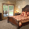 The master bedroom is done in warm tones and includes a view of the patio.