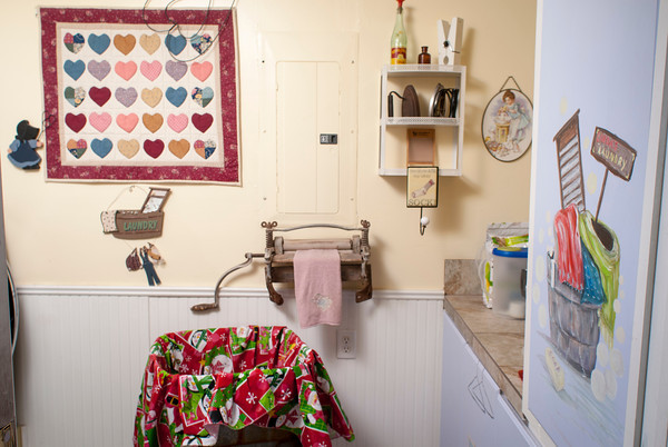 The laundry room contains a variety of antique items as well as a painting on the door by Linda Johnson's mother, Ginger McKenzie.