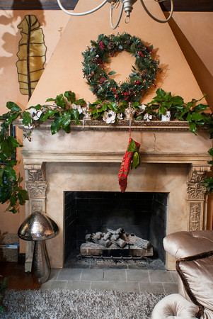 A magnolia garland and large wreath adorn the fireplace in the living room of the Newhouse home.