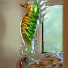 Small items reminiscent of the sea, such as this glass seahorse, are scattered throughout the home.