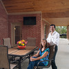 Dr. Caleb and Lisa Harris spend time on their patio covered by a tall wooden<br /> cathedral ceiling. The outdoor room includes a large television and they plan to add an outdoor kitchen.