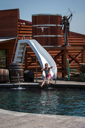 Kimber Hall shoots down the slide into the pool in her grandparent's backyard.