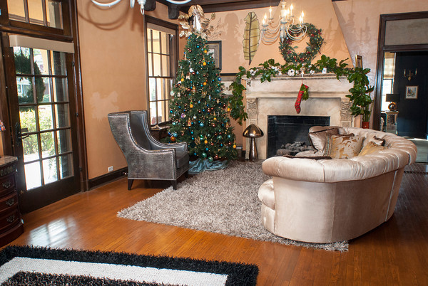 The living room just inside the front door has a large Christmas tree touching the top of the 11-foot beamed ceiling framed in by a large fireplace and a cozy seating area.