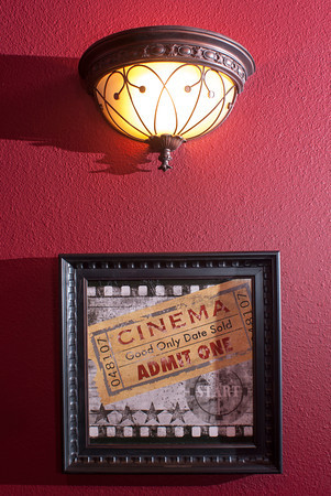 The home theater includes classic movie theater lighting fixtures and thematic framed art.