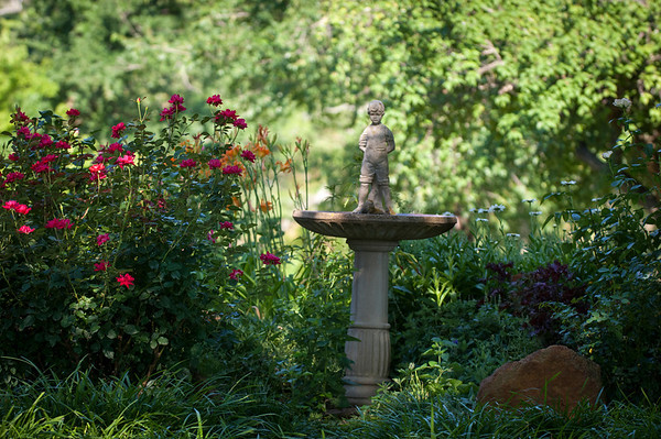 A birdbath is surrounded by roses, daylilies and other flowers.