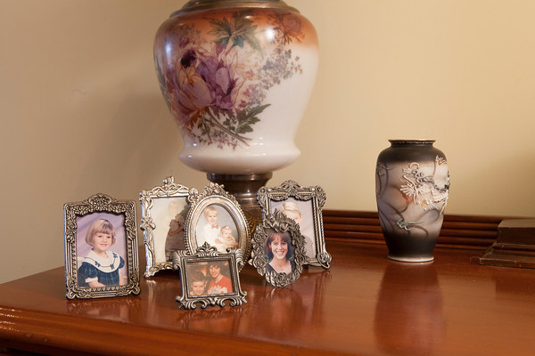 Petite frames holding family pictures in the upstair's hallway.