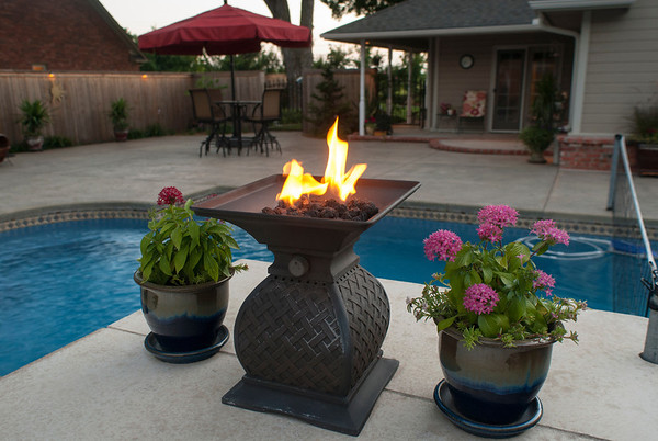 A flame burns by the pool as night falls.