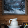A winter scene painted by Lottie Hufford hangs above one of the cabinets in the living room.