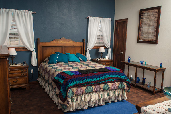 The bedroom in the Haley home displays blue and white walls, with aqua, turquoise and wood for accents.