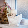 A Precious Moments figurine bathes on a window sill above the tub in the master bath.