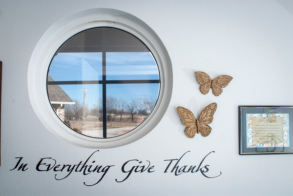 A circular window is framed with butterflies and an expression of faith.