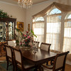 A trio of large windows coverd in sheer curtains lets natural light flood the formal dining room.