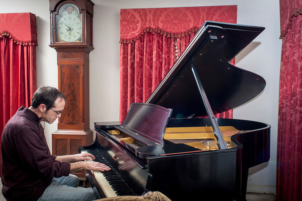 Ron Boren plays the grand piano in his home.