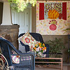 A large porch wraps around the front corner of the rock cottage of La Ferme at Fern Mountain, owned by Trudy and B.P. Sudberry. Trudy has decorated with painted wicker, colorful cushions and knotty alderwood shutters on the windows.