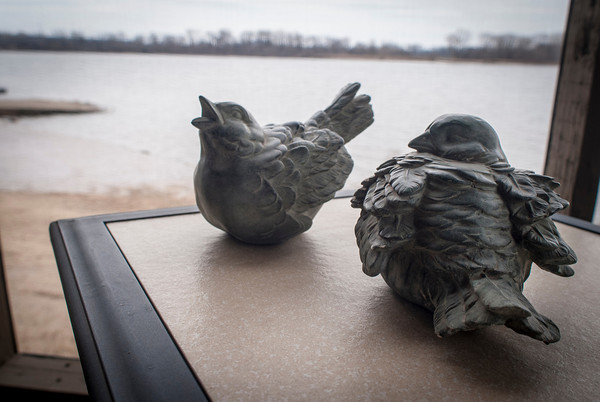 A pair of ceramic birds look out on the river from the screened porch of the Wright home.