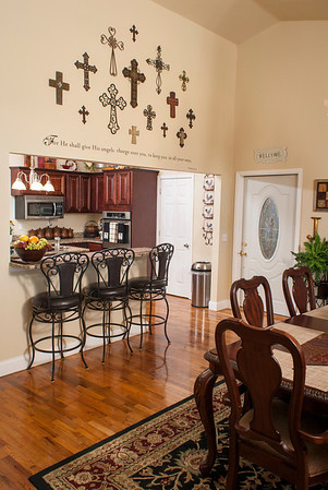 """A collection of 15 crosses adorns a wall in the dining room above the entryway to the kitchen.  Underneath the crosses is Psalms 91:11: """"For He shall give His angels charge over you, to keep you in all your ways."""""""