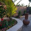 Raised beds filled with dramatic plantings flank the patio area.