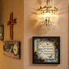 A wall sconce made with tear-drop glass elements lights one wall in the master bath. Signs and symbols of the Humphreys' faith are found throughout the home.