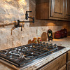 The cooktop include a pot-filling fixture and a travertine backsplash.